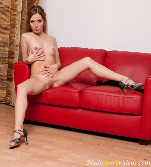 Hot redhead babe in the dance shoes posing on the sofa